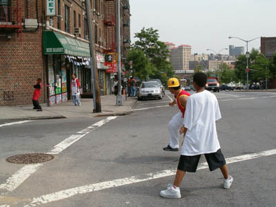 Some kids playing baseball in the middle of an intersection in the Bronx, New York City.